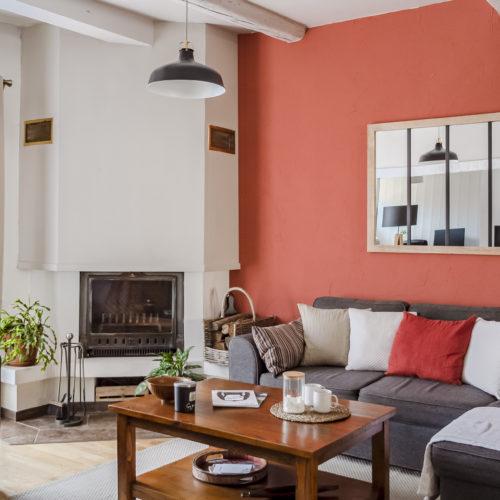 """Aménagement d'un salon. Le mur de couleur """"poterie"""" apporte de la luminosité et beaucoup de chaleur à cette pièce de vie."""